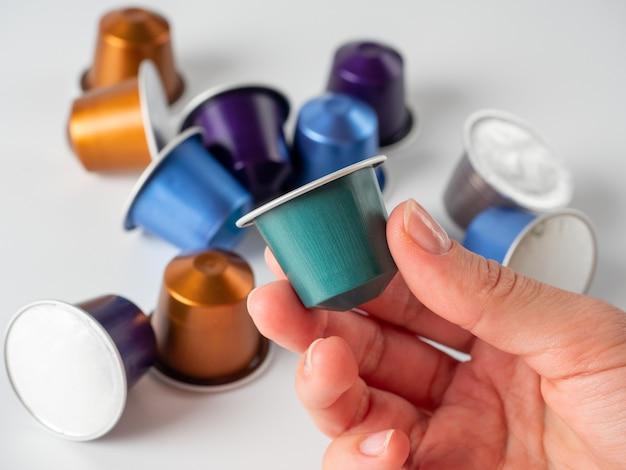 挽いたコーヒーを手にした色付きのアルミカプセル。その上に横たわっている他のカプセルと白い背景。コーヒーを作る現代の方法。コーヒーメーカー用カプセル Premium写真