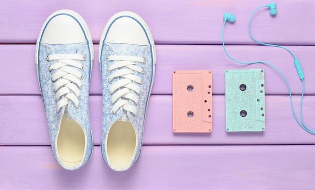 Цветные аудио кассеты, наушники, кроссовки обувь на фиолетовом фоне пастельных. старомодные технологии. вид сверху. квартира лежала.