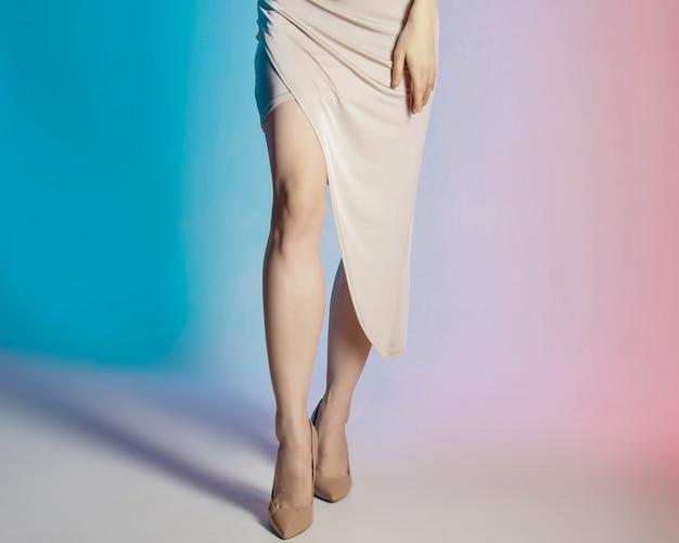 Цветной фон, неоновые огни, студийный снимок. модный портрет молодой элегантной женщины брюнет.