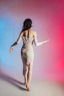 色付きの背景、ネオンライト、スタジオショット。若いエレガントなブルネットの女性のファッションの肖像画。