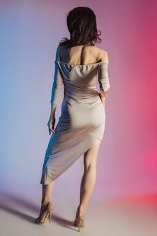 Colored background, neon lights, studio shot. fashion portrait of a young elegant brunette woman.