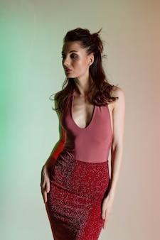 Цветной фон, неоновые огни, студийный снимок. портрет молодой элегантной брюнетки