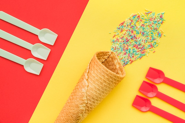 スプーン、アイスクリーム、コーンのある色付きの背景