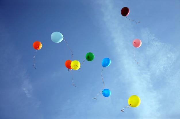 Цветные воздушные шары летят в голубом небе