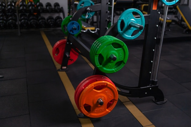 Colored barbell discs on racks in a modern gym