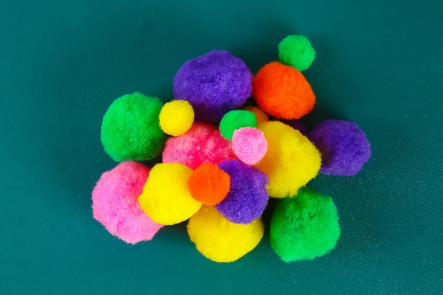 Colored beautiful pompons on a teal . assortment of pompons.