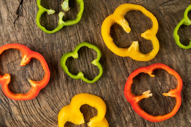 Colored bell pepper slided on wood background