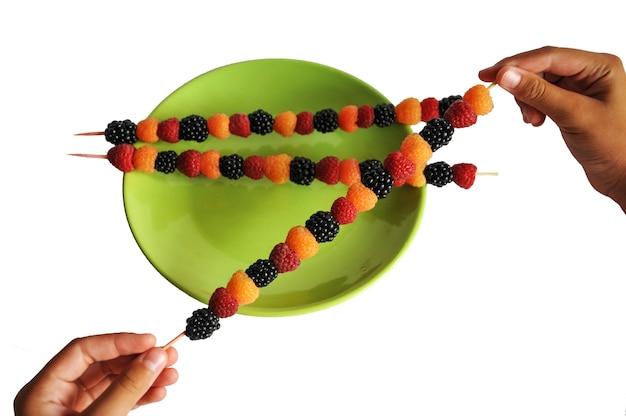Цветные ягоды насажены на деревянную палочку в руке и в зеленой тарелке