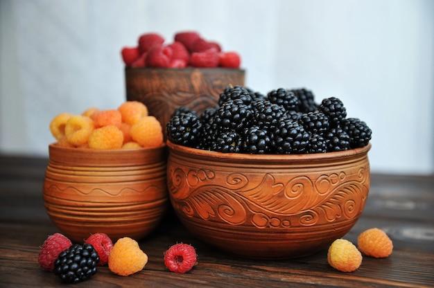 Цветные ягоды красно-желтой и черной малины или ежевики в фаянсе на деревянном столе