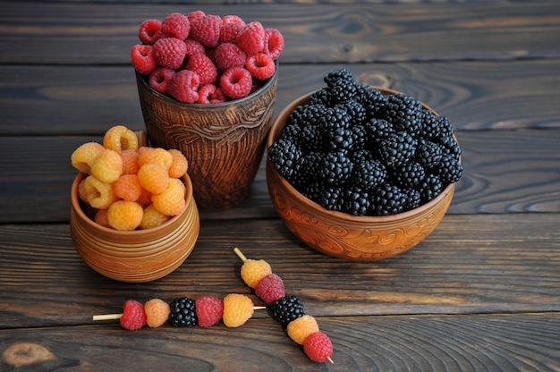 Цветные ягоды красно-желтой и черной малины или ежевики в фаянсе