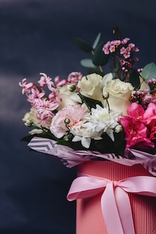 Colored bouquet in basket on dark background