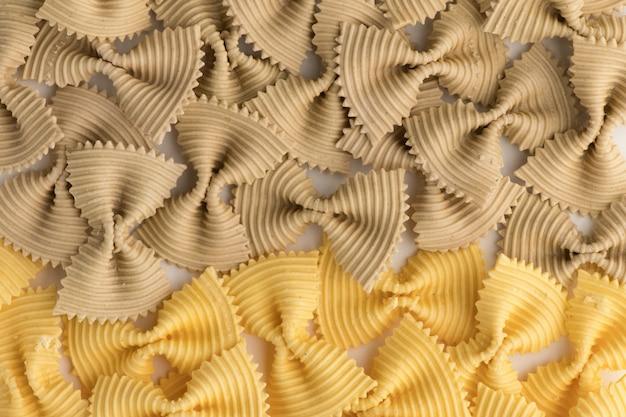 色付きの蝶ネクタイパスタ。白い背景で隔離のクローズアップ複数のファルファッレ。