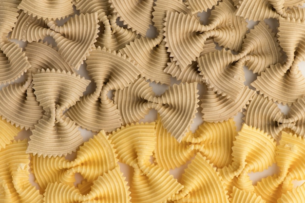 Colored bow tie pasta. closeup multiple farfalle isolated on white background.