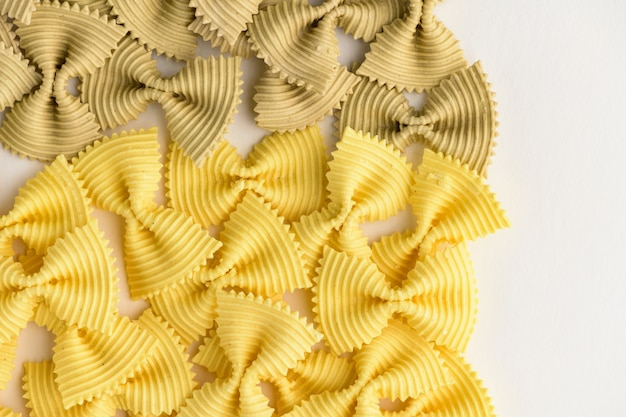 Colored bow tie pasta. closeup multiple farfalle isolated.