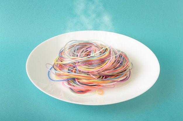 Colored cables on a plate from which steam comes out on a blue background. a concept inspired by spaghetti and food. minimal photography style.