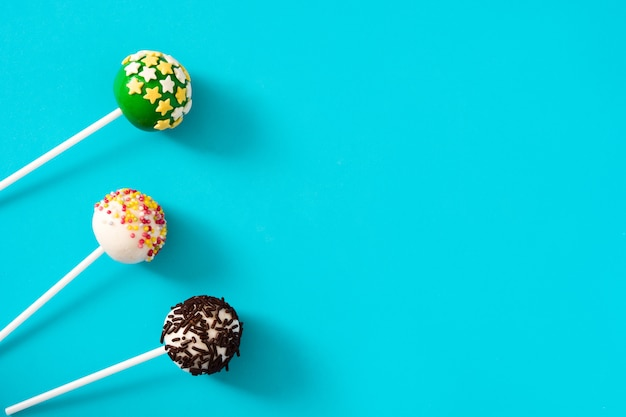 Colored cake pops on blue background copy space