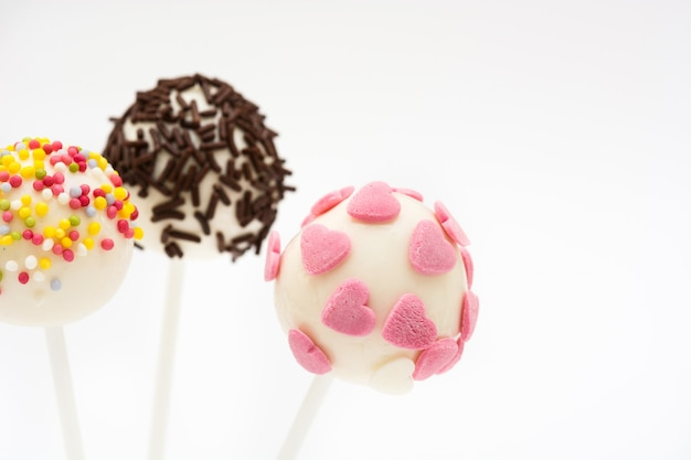 Colored cake pops on white surface