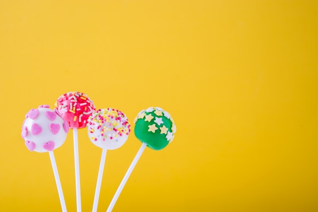 Colored cake pops on yellow background copy space
