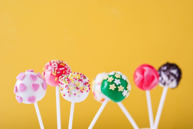 Colored cake pops on yellow background