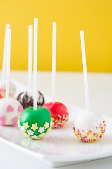 Colored cake pops on yellow wall