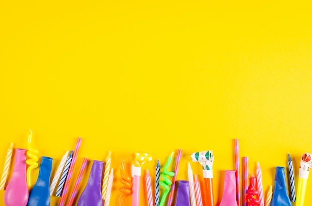 Colored candles and air balloons composition on yellow background, party and celebration decoration.