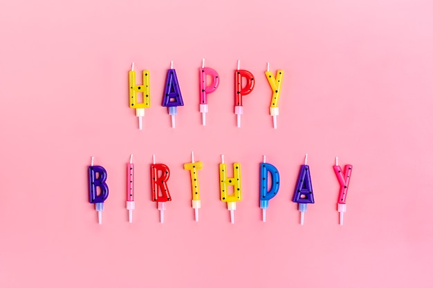 Colored candles on cake in form of letters happy birthday on pink