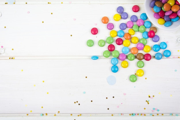 Colored candy bonbons scattered on white wooden board surface studio photo