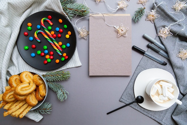 Colored candy canes, cookies, christmas garland lights, blank notebook,  coffee cup and fir branches