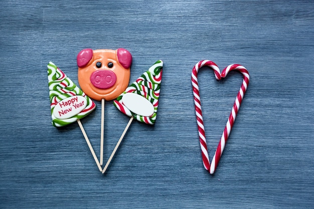 Colored candy lollipops new year's sweets on a blue background. christmas tree, lollipops and pig. sweet sucker, sweet heart of lollipops