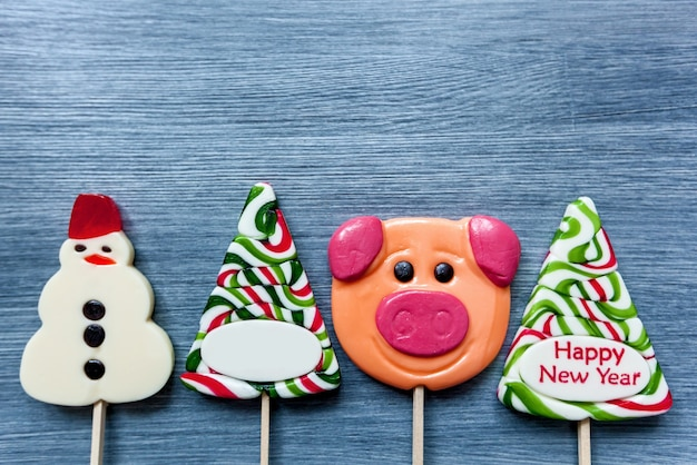 Colored candy lollipops new year's sweets on a blue background. christmas tree, snowman, pig and lollipops. sweet sucker