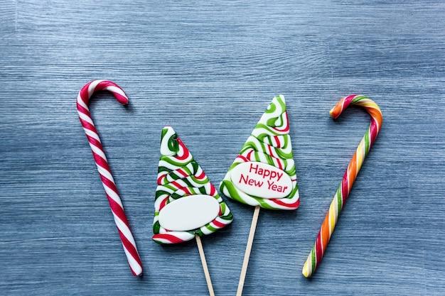 青い背景の上の色付きキャンディーロリポップ新年のお菓子クリスマスツリー雪だるま