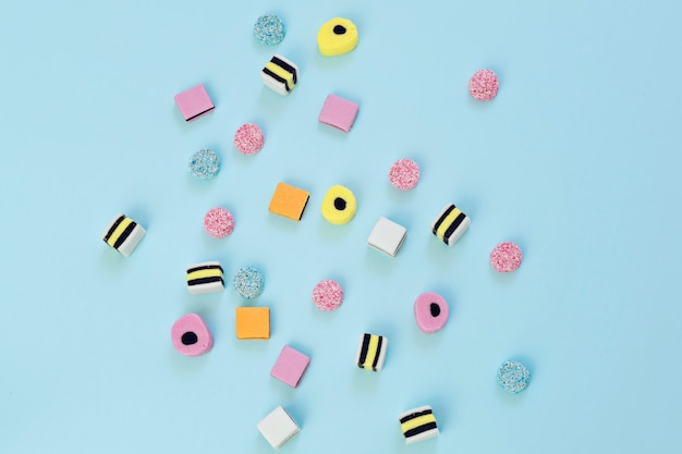 Colored candy scattered on the blue background