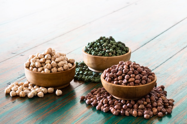Colored chickpeas (red, green, white) in wooden bowls on rustic background.