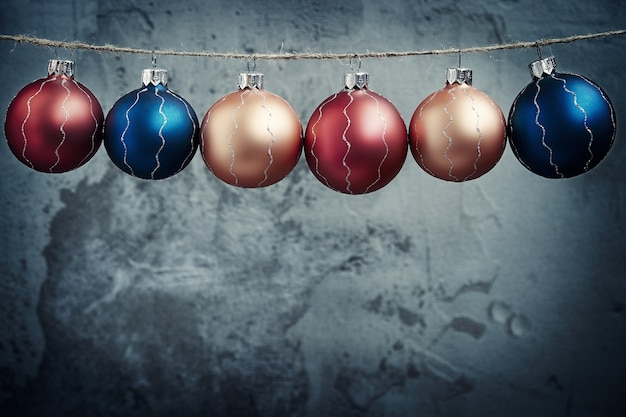 Colored christmas balls hanging on concrete wall background