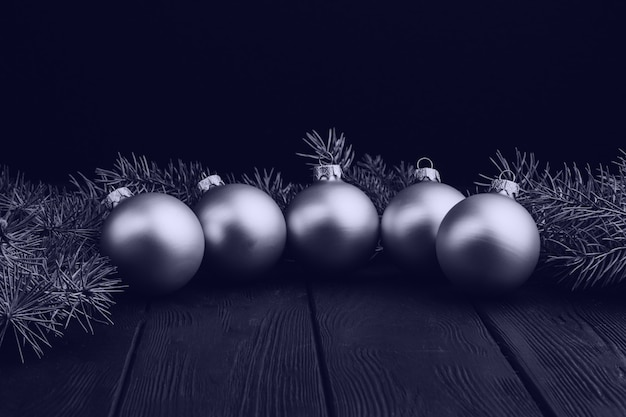 Colored christmas decorations on black wooden table. xmas balls on wooden background