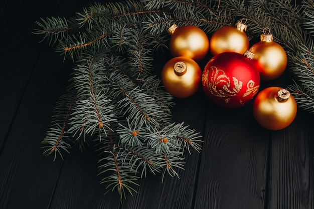 Colored christmas decorations on black wooden table. xmas balls on wooden background.