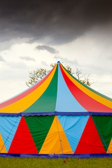 Colored circus tent in a rainy day with a rainbow on the sky