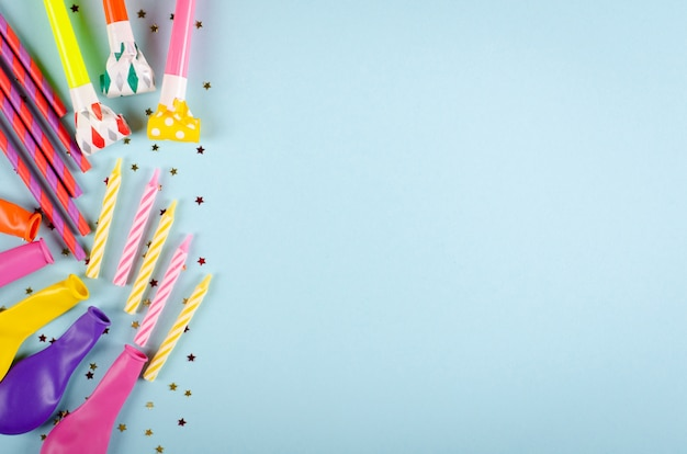 Colored confetti and air balloons composition on blue background, party and celebration decoration.