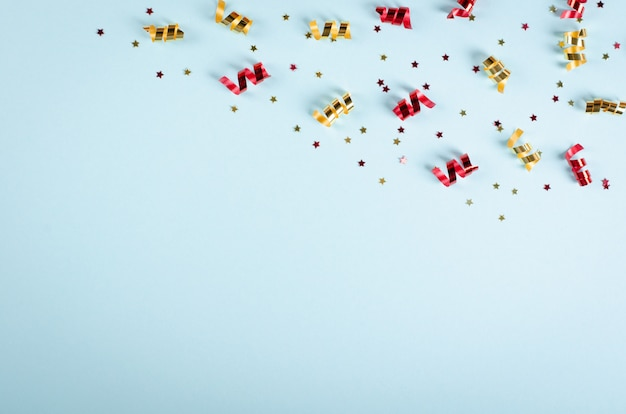 Colored confetti composition on blue background, party and celebration decoration.