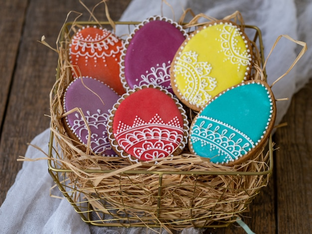 Colored cookies in the form of easter beautiful eggs with icing lace in a metal golden basket with straw on wooden table. close up, selective focus, copy space