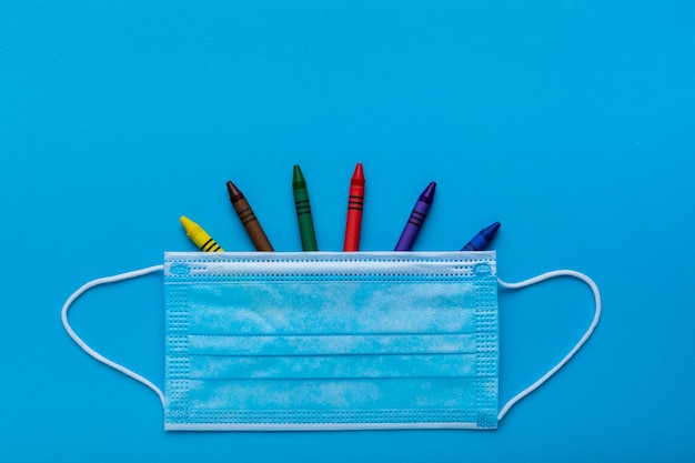 Colored crayons with a protective face mask as a symbol of back to school in a pandemic time