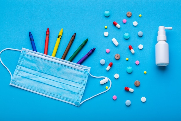 Colored crayons with a protective face mask as a symbol of back to school