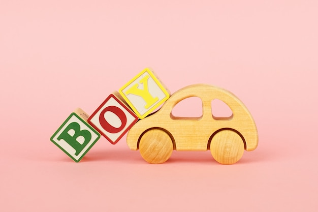 Colored cubes with letters boy and car toy on a pink