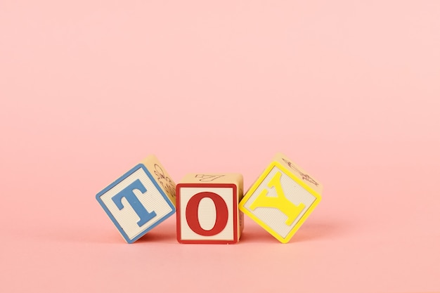 Colored cubes with letters with the inscription toy on a pink