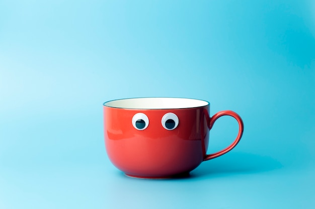Colored cup on an empty colored background, minimal concept background. home cookware and morning idea.
