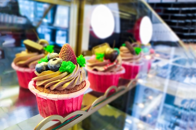 Colored cupcakes with blueberries and strawberries on the showcase with desserts in the cafe. baking in the pastry shop.