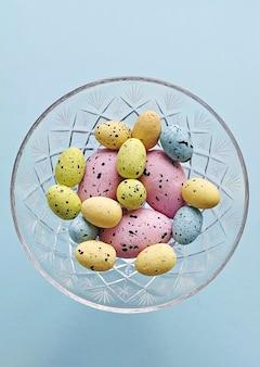 Цветные декоративные пасхальные яйца в хрустальной вазе на синем фоне, вид сверху. пасхальное украшение дома своими руками