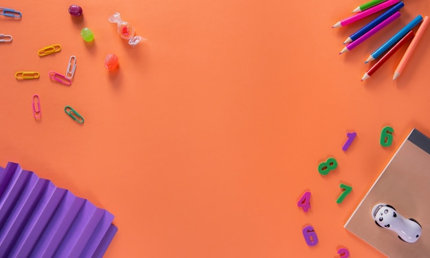 Colored different school supplies on orange background. back to school background. flat lay, top view