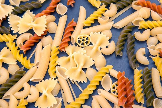 어두운 배경에 색된 다른 유형의 이탈리아 파스타. 음식 질감. 밀가루 제품 및 요리 식품