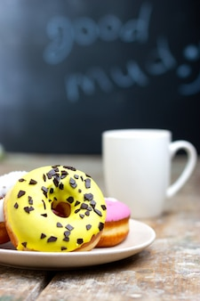 Colored donuts on a plate with a cup of coffee on a wooden table breakfast in a cozy coffee shop